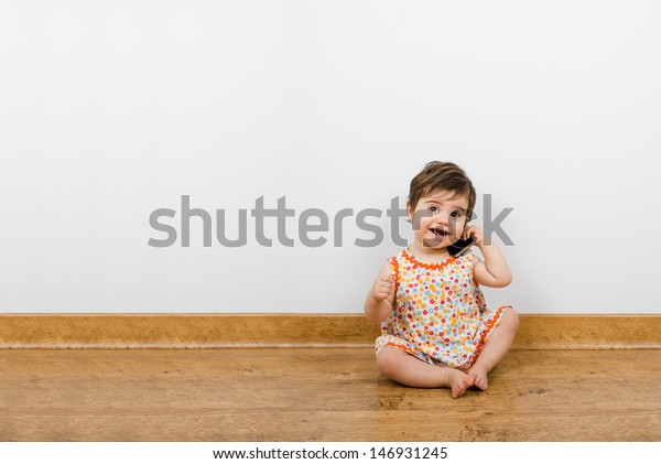 Pretty baby smiles and talk by phone with a lot of copyspace