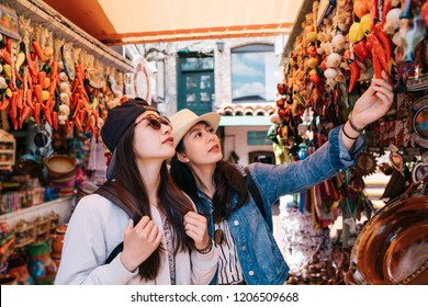 pretty backpackers buying chili decorations in the traditional market. two travelers shopping in a colorful vendor. Mexican decorations shop in USA.