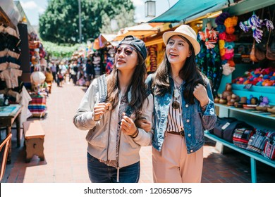 pretty backpackers cheerfully shopping in the Mexican street together. travelers visitingfamous Mexico street in trip. summer holiday travel in America.