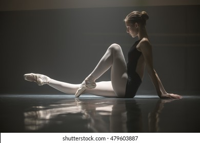 Pretty ballerina sitting on the floor in the dance hall. She leans her hands on the floor from the back while pulling one leg forward and the other bent at the knee. She is reflected on the floor