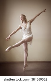 Pretty ballerina in a white tutu making a pose in a hall. Daylight falls on her. Indoor. Horizontal. retro treatment