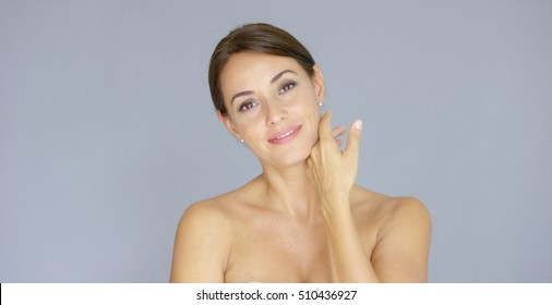 Pretty bare shouldered woman with fingers on neck