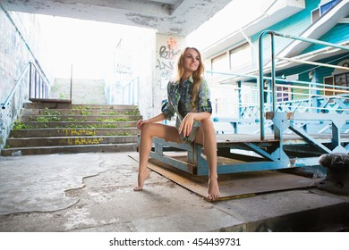 Pretty barefoot blond woman in shirt posing outdoors