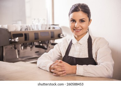 Pretty barista is smiling at camera at the coffee shop.