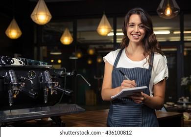 Pretty barista taking notes near coffee machine in coffee shop