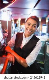 Pretty barmaid smiling at camera in a bar