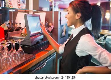 Pretty barmaid using touchscreen till in a bar