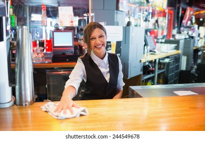 Pretty barmaid wiping down bar in a bar