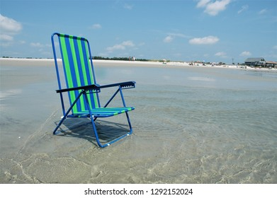 Pretty beach chair sitting in the surf at the seashore.