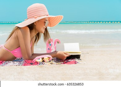 Pretty beautiful asian woman wearing pink swimwear bikini living sunbathe and reading a book on the beach in the summer, travel holidays concept