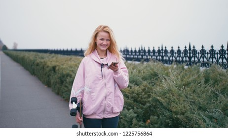 Pretty beautiful blond hipster woman with skateboard longboard using her smartphone cell phone for browsing, sms or chatting.