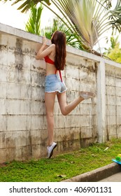 Pretty beautiful girl in red bra bikini, trendy sunglasses and short denim shorts trying climb up a stone wall. Urban scene, city life. Cute attractive sexy hipster lady look over high fence.