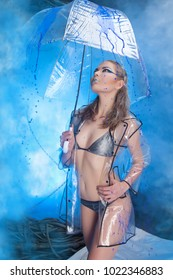 Pretty Beautiful Girl Under the Rain Wearing Transparent Coat and Standing with Umbrella in Blue Smoky Background