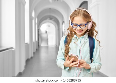 Pretty, beautiful school girl listening music with headphones in break between lessons. Happy girl in glasses holding phone, smiling and standing in hallway of school.