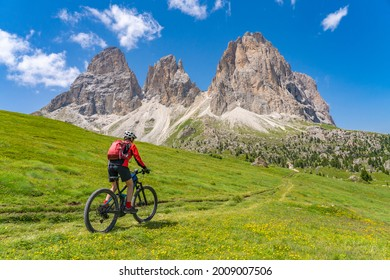 pretty beautiful senior woman riding her electric mountain bike below famous Sassolungo summit in Sella Dolomites  of Selva Wolkenstein, Val Gardena, South Tirol and Trentino, Italy