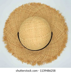 Pretty beautiful straw hat with black ribbon and bow on white background, beach hat from a side top view
