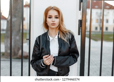 Pretty beautiful young blond woman in a black spring stylish jacket in black jeans in white shirt stands near the vintage iron gate at sunset. Fashionable girl. American fashion