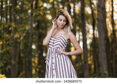 Pretty beautiful young blond woman in a vintage pink striped sundress stands in the forest among the trees on a bright sunny summer day. Glamorous happy girl resting outdoors.