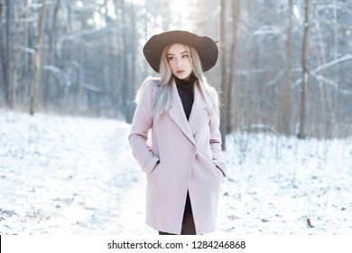 Pretty beautiful young woman in stylish warm glamorous clothes is walking in an elegant hat in a snowy forest on a winter sunny day. Fashionable attractive modern girl.