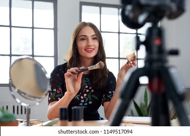 Pretty beauty vlogger recording make-up tutorial promoting product, social media marketing