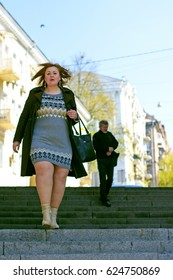 Pretty big woman of size plus size walks in the city, enjoys a sunny day and good weather in the rhythm of a big city life, cars and roads finds happiness in every day