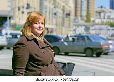 Pretty big woman of size plus size walks in the city, enjoys a sunny day and good weather in the rhythm of a big city life, cars and roads finds happiness in every da