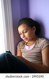 pretty biracial girl looking at her cell phone