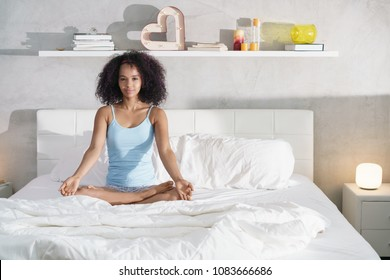Pretty black girl with curly hair sitting in bed in the morning. Beautiful young African American woman doing yoga after good sleep.