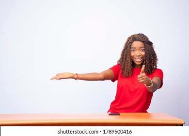 pretty black lady gestures to the space at her side and gives a thumbs up, advertising concept