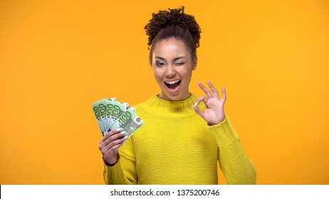 Pretty black lady showing bunch of euros and ok gesture, cash-back service