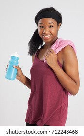 Pretty Black woman in exercise outfit with water bottle and towel, smiling with joy