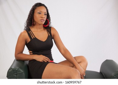 Pretty black woman in a black outfit and red accessories, sitting on a green bench and looking at the camera with a friendly expression