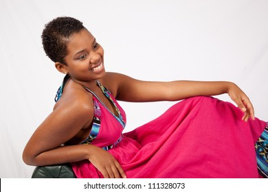 Pretty black woman in red dress relaxing and leaning back on a couch, looking at the camera with a friendly and happy smile