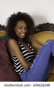 Pretty Black woman sitting on a couch looking happy