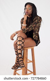 Pretty Black woman sitting on a stool and looking thoughtful