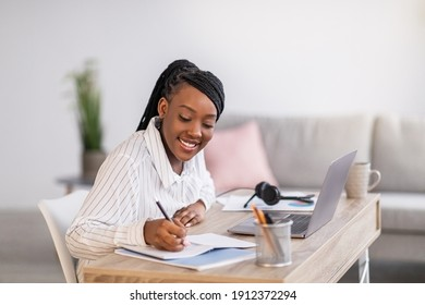 Pretty black woman student studying in front of laptop, taking notes and smiling, side view, copy space. Cheerful african american young lady attending webinar while staying home during lockdown