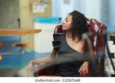 Pretty black woman with trendy dreadlocks and in dress sitting relaxed in leather armchair and looking away