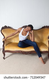 Pretty Black woman in a white blouse and blue jeans, sitting on a couch with a thoughtful expression