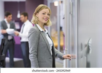 Pretty blond businesswoman open de door in modern office. Concept