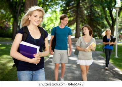 Pretty blond college girl looking at camera with friends in background