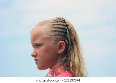 A pretty blond girl with braids in her hair on the beach in Tonsupa, Ecuador