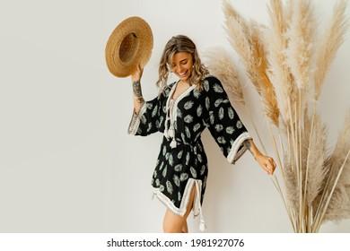 Pretty  blond girl dancing and having fun in studio on white background. Wearing boho dress, straw hat.  Summer mood.
