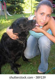 Pretty blond girl with dog licking her face