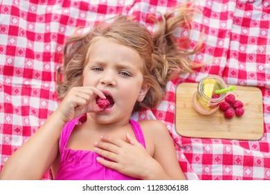 Pretty blond girl lying and eating ripe raspberries