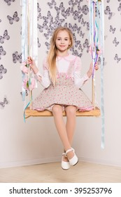 Pretty blond girl posing on the swing