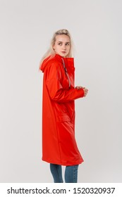 Pretty blond girl in a red raincoat standing isolated over white background. Get ready for bad weather.