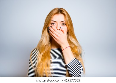 Pretty blond girl in shock closing mouth with hands