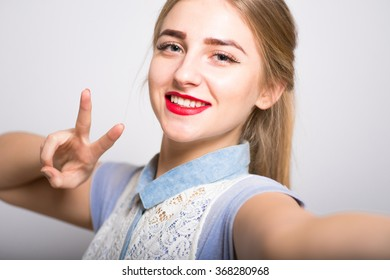 Pretty blond girl showing two finger gesture, isolated
