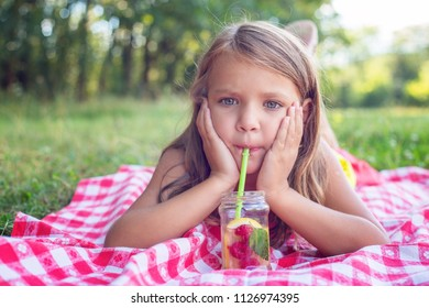 Pretty blond girl sipping lemonade from a jar on a hot summer day