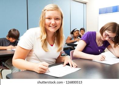 Pretty blond girl sitting in her high school class.